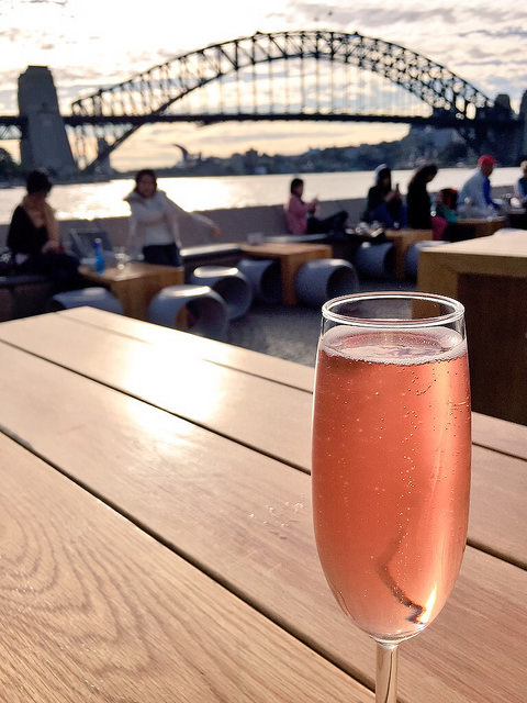 Enjoying a drink by Sydney Harbour, sparking pink moscato